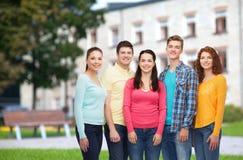 Groep glimlachende tieners over campusachtergrond Royalty-vrije Stock Fotografie