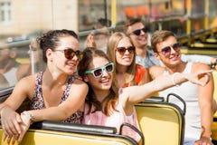Groep glimlachende vrienden die door reisbus reizen Stock Afbeeldingen
