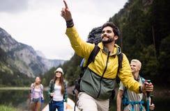 Groep glimlachende vrienden die met rugzakken in openlucht wandelen Reis, toerisme, stijging en mensenconcept royalty-vrije stock foto