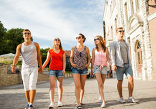 Groep glimlachende vrienden die in stad lopen Stock Foto's