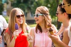 Groep glimlachende vrienden met roomijs in openlucht Stock Foto's