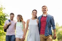 Groep glimlachende vrienden met rugzak wandeling stock afbeeldingen