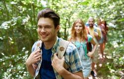 Groep glimlachende vrienden met rugzakken wandeling Stock Fotografie