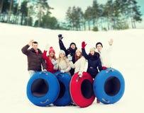 Groep glimlachende vrienden met sneeuwbuizen Stock Afbeelding