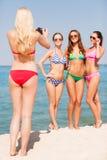 Groep glimlachende vrouwen die op strand fotograferen Royalty-vrije Stock Foto