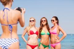 Groep glimlachende vrouwen die op strand fotograferen Stock Afbeeldingen