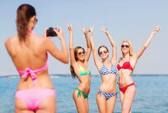 Groep glimlachende vrouwen die op strand fotograferen Royalty-vrije Stock Foto's