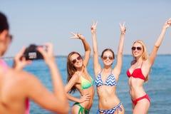 Groep glimlachende vrouwen die op strand fotograferen Royalty-vrije Stock Afbeelding