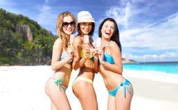 Groep glimlachende vrouwen die roomijs op strand eten Stock Foto