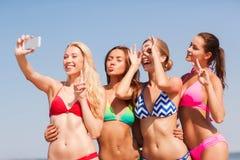 Groep glimlachende vrouwen die selfie op strand maken Stock Afbeeldingen