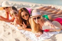 Groep glimlachende vrouwen met smartphone op strand Stock Afbeeldingen