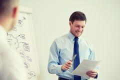 Groep glimlachende zakenlieden die in bureau samenkomen Stock Foto