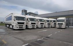 Groep gloednieuwe die vrachtwagens voor bedrijfhoofdkwartier worden geparkeerd Stock Foto's