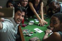 Groep gok in casino spelen en mensen die selfie nemen royalty-vrije stock fotografie