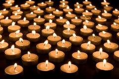 Groep het branden van kaarsen bij een zwarte achtergrond Stock Afbeeldingen