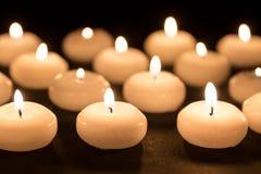 Groep het branden van kaarsen bij zwarte achtergrond Stock Foto