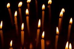 Groep het branden van kaarsen in dark royalty-vrije stock afbeelding
