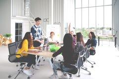 Groep het jonge Aziatische creatieve team spreken, brainstorming, delend of opleidend op vergadering of workshop op kantoor Geluk royalty-vrije stock afbeeldingen