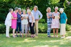 Groep hogere mensen die hun schilderijen samen met cursusinstructeur bespreken, terwijl status in tuin op zonnige dag stock fotografie