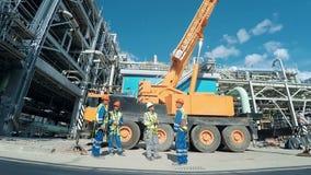 Groep indusrial arbeiders die bij een bouwterrein spreken Industriële scèneachtergrond stock video