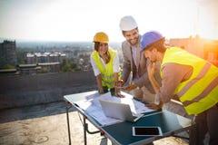 Groep ingenieurs, architecten, partners bij bouwwerf die samenwerken royalty-vrije stock foto's