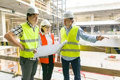 Groep ingenieurs, bouwers, architecten op het bouwterrein Bouw, ontwikkeling, groepswerk en mensenconcept stock afbeeldingen
