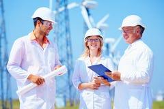 Groep ingenieurs op windenergiepost Stock Foto's