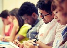 Groep internationale studenten die bij lezing schrijven stock foto's