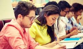 Groep internationale studenten die bij lezing schrijven stock fotografie