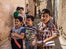 Groep Iraanse Leerlingen, jongens, de primaire en en middelbare schoolstudenten die, die één holding een studienotitieboekje, in  stock fotografie