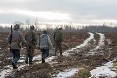 Groep jagers die op het gebied lopen Stock Afbeeldingen