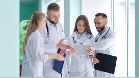Groep jonge artsen met stethoscoop die iets bespreken die het scherm van tabletpc bekijken stock videobeelden