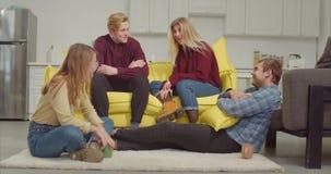 Groep jonge babbelende vrienden die thuis ontspannen stock video