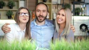 Groep jonge bedrijfs en vrienden die stellend voor foto middelgroot schot glimlachen koesteren stock videobeelden