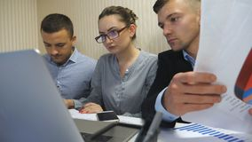 Groep jonge bedrijfsmensen die bij lijst in modern bureau zitten en aan nieuw project werken De collega's herzien zorgvuldig stock videobeelden