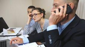 Groep jonge bedrijfsmensen die bij lijst in modern bureau zitten en aan nieuw project werken De collega's kijken zorgvuldig stock video