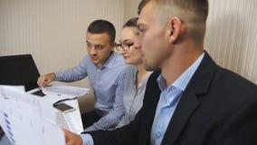 Groep jonge bedrijfsmensen die bij lijst in modern bureau zitten en aan nieuw project werken De collega's kijken zorgvuldig stock videobeelden