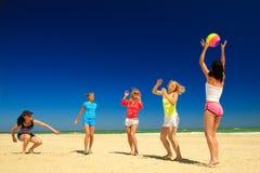 Groep jonge blije meisjes die volleyball spelen Stock Afbeeldingen
