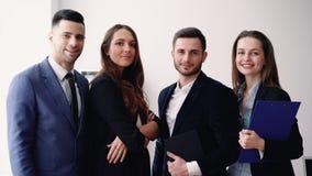 Groep jonge en glimlachende bedrijfsmensen in modern bureau stock footage