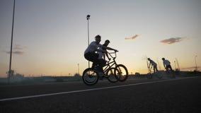 Groep jonge fietsersvrienden die en op rokerige fietsen hangen berijden die stunts en ollie trucs doen bij de zonsondergang in la stock video
