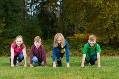 Groep jonge geitjes bij de beginnende lijn van een ras Stock Afbeelding