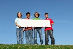 Groep jonge geitjes met leeg teken Stock Afbeeldingen