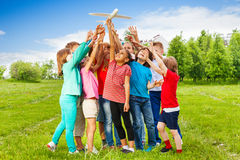 Groep jonge geitjesbereik na groot wit vliegtuigstuk speelgoed Stock Afbeeldingen