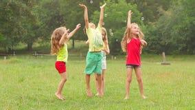 Groep jonge geitjesspel met zeepbels in een park Kinderen actief spel Langzame Motie stock footage