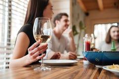 Groep jonge gelukkige vrienden die lunch hebben en wijnstok drinken Royalty-vrije Stock Fotografie