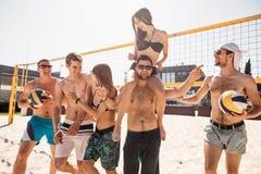 Groep jonge gelukkige vrienden die op het hof van het strandvolleyball na gewonnen spel lopen royalty-vrije stock foto