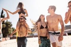 Groep jonge gelukkige vrienden die op het hof van het strandvolleyball na gewonnen spel lopen stock afbeelding