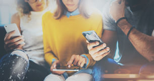 Groep jonge hipsters die op de Engelse handen van de bankholding zitten en elektronische gadgets gebruiken Het concept van het Co royalty-vrije stock afbeeldingen
