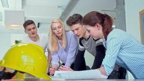 Groep jonge ingenieurs die architecturale blauwdrukken bespreken stock footage