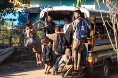 Groep jonge jongens die school op een schoolbus in het dorp van Akat Amnuai, Sakon verlaten royalty-vrije stock foto's